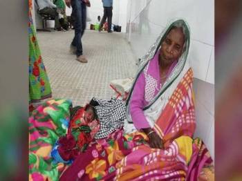 Ramisa duduk di koridor hospital bersama cucunya.