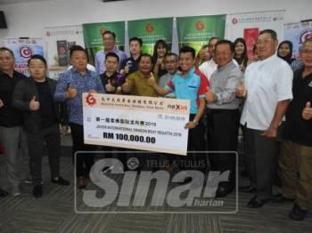 Rosleli (tengah) mewakili Kerajaan Negeri Johor menerima mok cek penajaan berjumlah RM100, 000 pada Majlis Promosi 1st International Dragon Boat Regatta 2019.