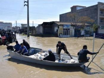 Penduduk Kampung Agh Ghaleh di utara Iran menggunakan bot bagi mengharungi jalan yang dinaiki banjir.- Foto AFP