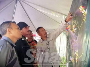 Khairul Anwar (kanan) ketika melihat laluan check point yang digunakan bagi penganjuran Gopeng Ultra Trail.