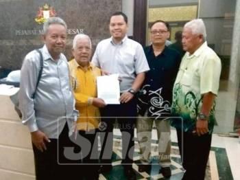 Md Said (dua, kiri) menyerahkan surat bantahan ketua kampung kepada wakil Menteri Besar Johor.