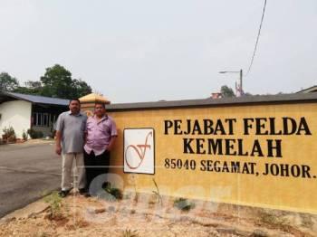 Azman (kanan) bersama Pengurus Felda Kemelah, Ishak Hassan di hadapan Pejabat Felda Kemelah.