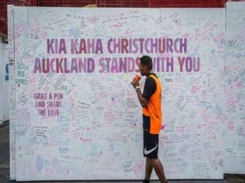 Seorang lelaki melihat dinding khas di Auckland yang dipenuhi pesanan bagi memperingati mangsa serangan berdarah di Christchurch.