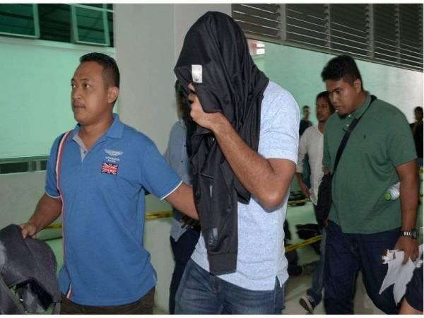 Ketua balai polis berpangkat Inspektor di Balai Polis Kajang Mohd Alfian Mohd Zainal 34 (tengah), dihadapkan ke Mahkamah Sesyen hari ini atas dua pertuduhan menerima rasuah berjumlah RM1,000 daripada pengusaha rumah urut, tiga tahun lepas. - Foto Bernama
