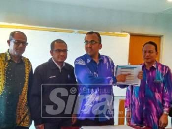 Mohd Rafiq (tengah) menunjukkan laporan penyumbang utama FDI pada tahun lalu.