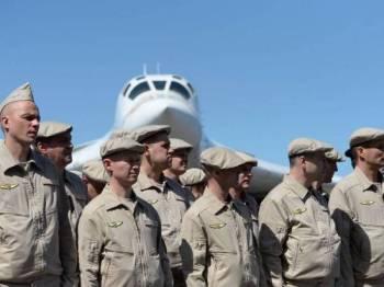 Pegawai Tentera Udara Rusia berdiri di hadapan pesawat pengebom supersonic sejurus mendarat di Lapangan Terbang Antarabangsa Maiquetia di utara Caracas.