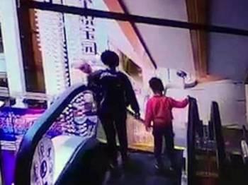 Ibu mangsa gagal berdiri dengan stabil dan menyebabkan anaknya terjatuh dari eskalator yang sedang bergerak.