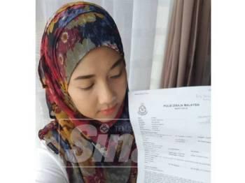 Anisa menunjukkan laporan polis yang dibuat selepas akaun banknya digodam dan berlaku transaksi tanpa kebenaran.