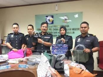 Azizan (tengah) menunjukkan sebahagian beg tangan wanita tiruan yang dirampas pihaknya dalam operasi penguatkuasaan semalam. - Foto ihsan KPDNHEP