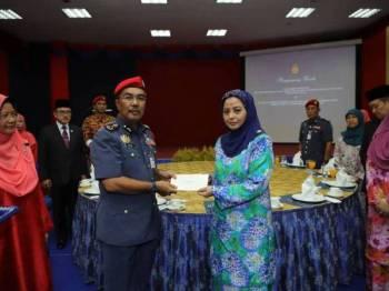 Raja Zarith menyampaikan cek sumbangan daripada Sultan Johor kepada Yahya. - FOTO: Royal Press Office