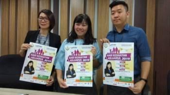 May Ing (tengah) menunjukkan poster Hari Kesihatan Keluarga Sepanjang Tahun bersama-sama Juliet (kanan) dan Kar Khan.