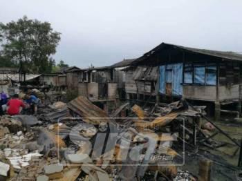 Penduduk melihat keadaan rumah mereka yang hangus terbakar.