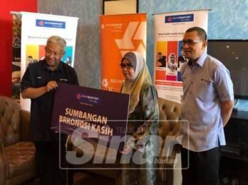 Amiruddin (kiri) menyampaikan sumbangan BRKongsi Kasih kepada bendahari UMT, Zahara Kedri berjumlah RM15,000 untuk diagihkan kepada mahasiswa universiti itu yang kurang berkemampuan.