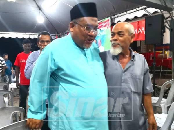 Zulkefly (kiri) bermesra dengan pengundi DUN Rantau di Bilik Gerakan di Taman Kelab Tuanku Mambau, malam tadi.