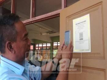 Mohd Razali menunjukkan kaedah menggunakan QR Code untuk pendaftaran kehadiran ibu bapa.