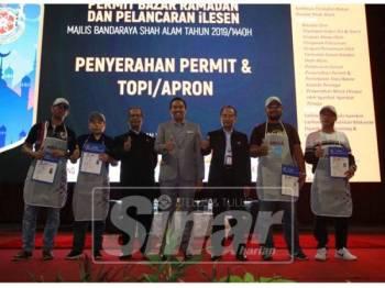 Mohd Rashidi (tengah) bersama sebahagian peniaga yang menerima permit dan mempraktikkan kaedah tatacara pemakaian yang betul mengikut sayarat-syarat ditetapkan MBSA.