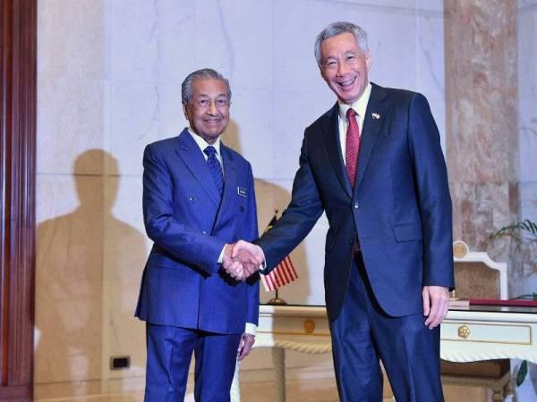 Perdana Menteri Tun Dr Mahathir Mohamad (kiri) bersalaman dengan rakan sejawatannya dari Singapura Lee Hsien Loong ketika perjumpaan bagi mengadakan perbincangan di bawah rangka kerja Pemukiman Pemimpin Malaysia-Singapura Kesembilan di Bangunan Perdana Putra hari ini.- Foto Bernama