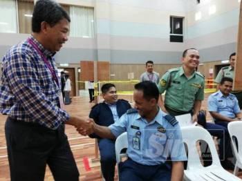 Mohamad memenui pengundi di Dewan Angkasaraya Pangkalan Udara Sendayan bagi meninjau proses pengundian awal PRK DUN Rantau hari ini: - Foto ADAM AMIR HAMZAH