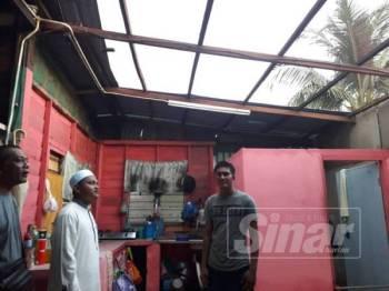 Ahmad Saqif (dua, kiri) meninjau keadaan bumbung rumah salah seorang mangsa di Kampung Sungai Baru, Selinsing yang terjejas teruk diterbangkan ribut lewat petang semalam.