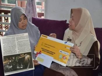 Farihah Che Husin (kanan) menyerahkan cek bayaran Faedah Pengurusan Mayat bernilai RM2,000 kepada ibu mangsa, Rohana Muda, di Bukit Payong, Marang, semalam. (Gambar kecil: Keratan akhbar Sinar Harian siaran 5 April lalu)