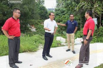 Mohd Zahir (dua, kiri) membincangkan isu pencemaran bau di longkang dan tapak pembuangan sampah haram yang berlaku di Jalan Mas 1, Kuala Lumpur hari ini. - FOTO: SWCorp