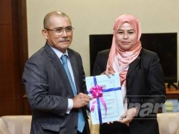 Bekas Pengerusi PAC, Datuk Seri Dr Ronald Kiandee bersama Pengerusi PAC baharu, Datuk Dr Noraini Ahmad memegang dokumen PAC. - Foto Sinar Harian Zahid Izzani