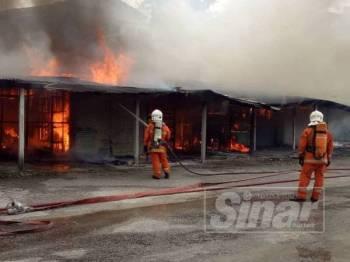 Anggota bomba memadamkan kebakaran membabitkan 11 gerai di Jalan Pasar, hari ini.