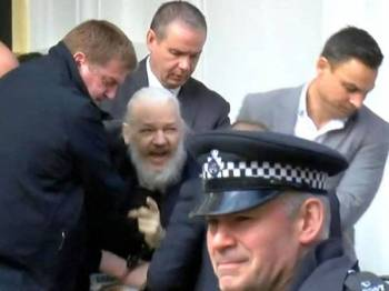 Julian Assange (tengah) ditahan di kedutaan Equador di London.