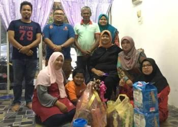 Mahsuri @ Baizura (depan, tengah) bersama beberapa ahli jawatankuasa menyampaikan sumbangan kepada keluarga mangsa kebakaran di Kampung Tok Fakir, Marang.
