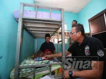 Amiruddin memeriksa barangan yang dibawa Mohd Firdaus ketika ditempatkan di bilik asrama Pertubuhan Badan Kebajikan Anak-anak Yatim Darussalam, hari ini.