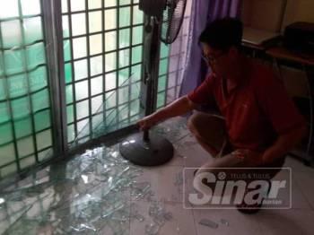 Siew Seng menunjukkan pintu kediamannya di Taman Rengit Jaya yang pecah akibat letupan dan kebakaran di tapak projek Rapid Pengerang.