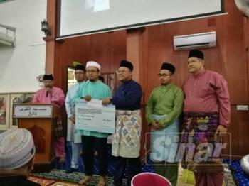 Amirudin menyampaikan sumbangan kepada masjid, surau dan madrasah di Masjid At-Taqwa, hari ini.