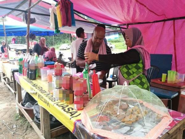 Mohd Nazri dan isterinya sedang memproses ais kacang.