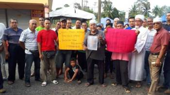 Peneroka turut memegang sepanduk pada himpunan aman di Felda Jerangau Dungun.