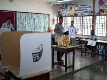Pengerusi Suruhanjaya Pilihan Raya (SPR) Azhar Azizan Harun (tengah) meninjau proses mengundi bagi PRK DUN Rantau di Pusat Mengundi Sekolah Kebangsaan Nyatoh hari ini. -Foto Bernama