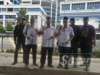 Masridzi (tiga, kiri) hadir membuat laporan polis di IPD Dang Wangi, berikutan isi penularan gambar yang dimuat naik di Facebook 'Sabah - Sarawak Merdeka'.