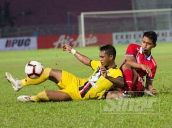 Pertahanan Kelantan, Mohd Shahrul Nizam Ros Hasni (kanan) mengasak daripada belakang pemain PDRM pada pertemuan kedua-dua pasukan dalam aksi Liga Premier di Kota Bharu, malam tadi.