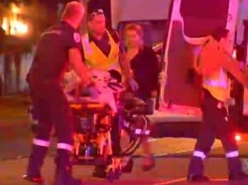 Anggota paramedik mengangkat seorang mangsa yang cedera.