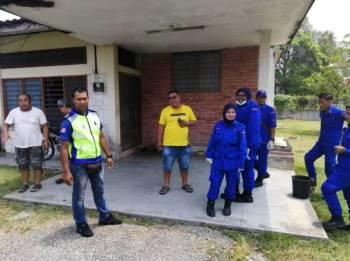Pasukan penyelamat dan jiran di hadapan rumah mangsa.