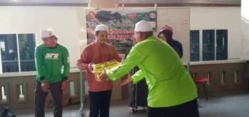 Sabri (dua dari kiri) menyampaikan sumbangan kepada asnaf di Masjid Putra Al Haj, Yan hari ini.