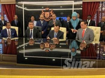 Osman menandatangani surat penyerahan kuasa sambil diperhatikan Sahruddin di Pejabat Menteri Besar Johor, Kota Iskandar, hari ini.