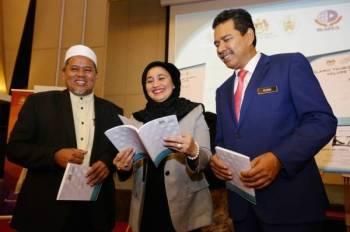 Abdul Khani (kanan) melihat jurnal pelancongan Islam bersama Haslina (tengah) selepas selesai perasmian Symposium On Islamic Tourism 2019 dan Majlis Pelancaran Islamic Tourism Journal Vol.1 2019 di Hotel Paya Bunga, di sini hari ini.