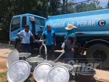 Sharifah Hazlina melihat pekerja LAP mengisi air dari tangki ke dalam bekas yang disediakan penduduk di hadapan rumah mereka