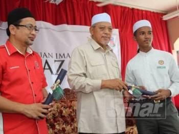 Ahmad (tengah) menyampaikan Skim Bantuan Imam Al-Ghazali kepada salah seorang pelajar cemerlang di Maahad Muhammadi Pasir Pekan, hari ini.