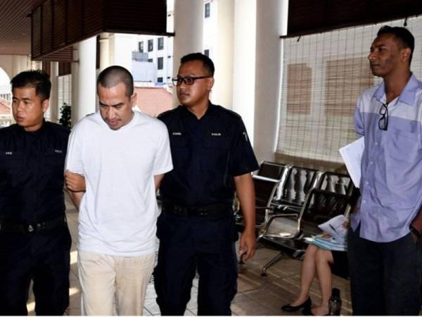Jurukamera RTM, Mohamad Amirul Amin Mohamed Amer, 31, (kanan) memerhatikan pengawal peribadi, Jaafar Haalid yang dibawa ke Mahkamah Tinggi George Town hari ini. Mohamad Amirul Amin hadir di mahkamah itu untuk memberi keterangan dalam kes saman yang difailkannya terhadap Jaafar dan syarikat GMP Kaisar Security (M) Sdn Bhd berhubung insiden tembakan di Lebuhraya Tun Dr Lim Chong Eu tiga tahun lepas. - Foto Bernama