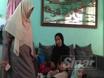 Haniza (kiri) ketika menziarahi ibu mangsa, Seri Sunarti (duduk) di rumah mereka di PPR Kota Damansara, Seksyen 8, hari ini.