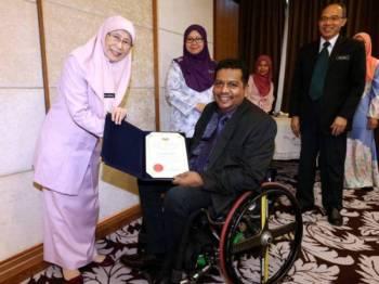Datuk Seri Dr Wan Azizah Wan Ismail (kiri) menyampaikan watikah pelantikan kepada seorang penerima selepas mempengerusikan mesyuarat Majlis Kebangsaan Bagi Orang Kurang Upaya (MKBOKU) semalam. - Foto Bernama