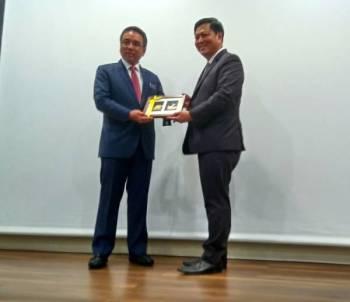 Adly (kiri) menerima cenderahati daripada Chee Hong ketika lawatan ke Infineon Technologies (M) Sdn Bhd di Batu Berendam, di sini, hari ini.