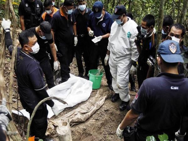 Anggota forensik Polis DiRaja Malaysia memeriksa jenazah yang ditemui di kubur yang tidak ditanda berhampiran Wang Kelian di puncak Bukit Wang Burma di Wang Kelian yang terletak di sempadan Malaysia-Thailand. - Foto fail AP