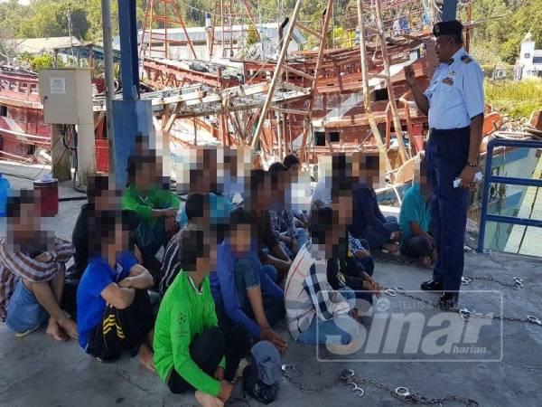 Pannir (kanan) menyoal siasat tekong dan awak-awak yang ditahan sebaik mereka tiba di jeti Zon Maritim Kemaman.